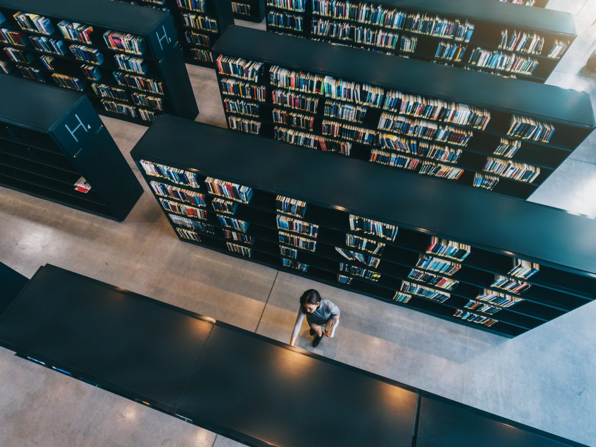 Young woman looking for a book in shelf